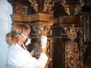 Olga Gago trabajando en la restauración de un retablo de madera.